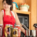 A waist up image of a mixed race (Caucasian, Asian, Pacific Islander) young adult woman canning homegrown fruits and vegetables.